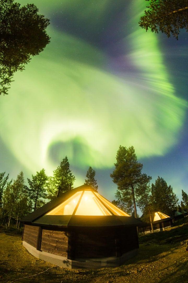 Crazy northern lights over aurora cottages at Aurora Village hotel Ivalo Lapland Finland.