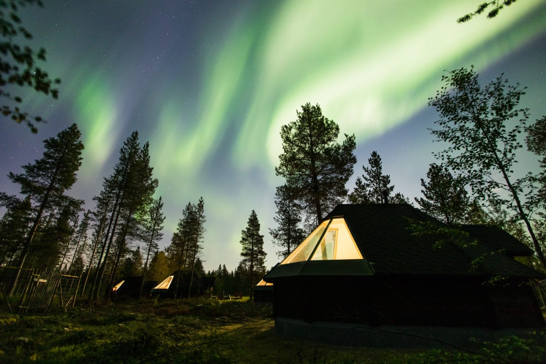 Northern lights shining bright over glass igloos at Aurora Village Ivalo Lapland Finland. Photo by All About Lapland.