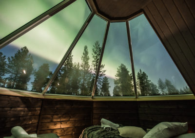 Watching the northern lights from inside the Aurora cabin at Aurora village resort in Ivalo Lapland Finland.Photo by All About Lapland.