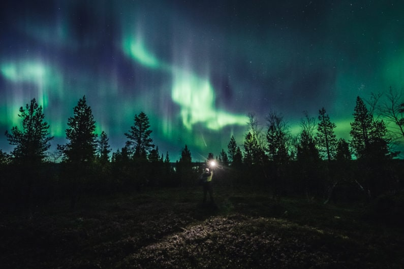 Alexander Kuznetsov from Aurora Hunting taking northern lights photo in Ivalo Lapland Finland.