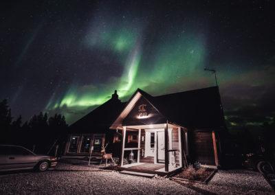 Aurora borealis dancing over Aurora Village's restaurant Loimi in Ivalo Inari Lapland Finland.