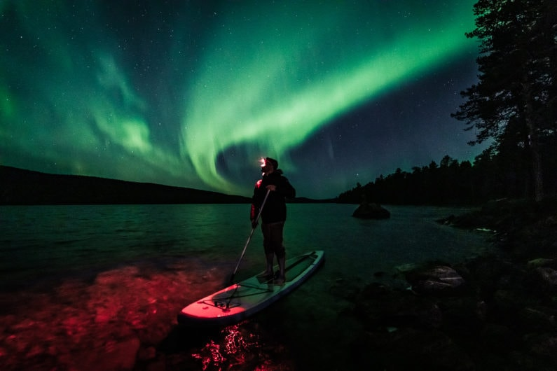 Floating under the aurora in Ivalo Lapland Finland.