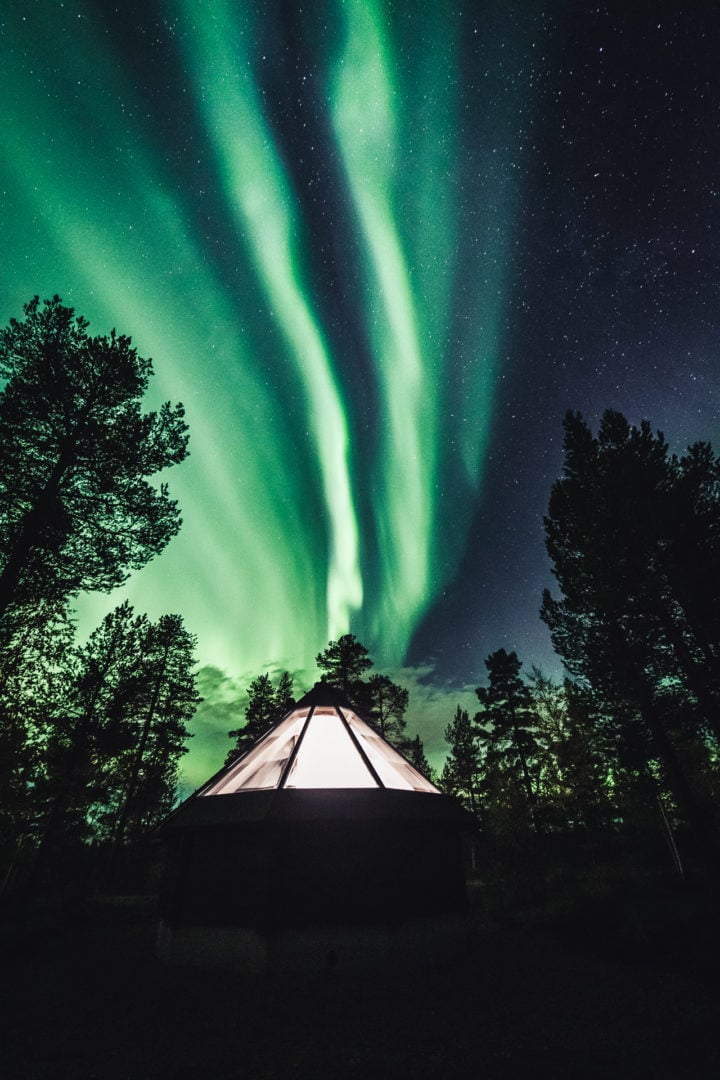 Magical northern lights over aurora cabin cottage at Aurora Village Ivalo Lapland Finland.