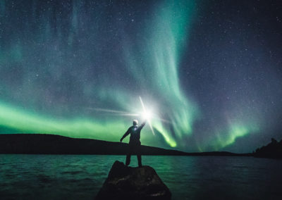 Alexander Kuznetsov on a rock welcoming the Northern Lights in Ivalo Lapland Finland.
